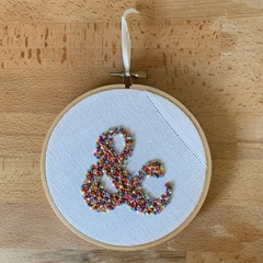 Hand stitched embroidered ampersand (and &) wall art in a hanging hoop