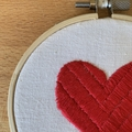 Hand stitched embroidered heart wall art in a hanging hoop