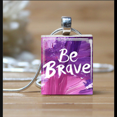 """BE BRAVE"", scrabble tile pendant. Comes with a pink satin necklace."