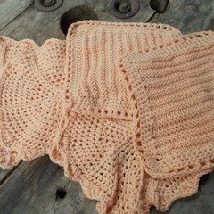 Crocheted or knitted washcloth made from bamboo fibre in soft peach yarn.