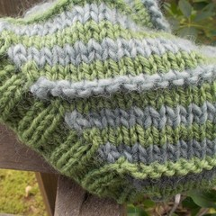 knitted baby beanie made from pure wool yarn. Greens and greys, slouch style.