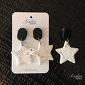 White stars with silver foil and black tops dangle earrings