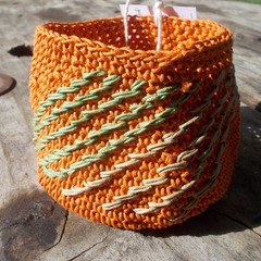 Crocheted bowl made from waxed cotton orange with biege and green embroidery