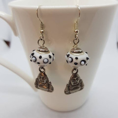 Silver buddha charm earrings dangling from glass pandora style beads.