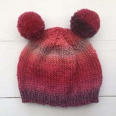 Shades of Pink Knit hat with two pom poms for a 6 month old approximately.