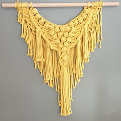 Yellow macrame wall hanging.