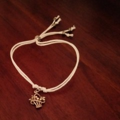 White cotton bracelet with sterling silver charm.