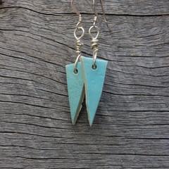 Unique handmade ceramic earrings. Bright pastel blue triangles.