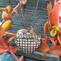 Dark silver metal puffy heart cage filled with rose quartz chips.