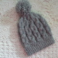 Baby's hand-knitted cable-knit beanie with pom pom to fit NB; 4-ply wool
