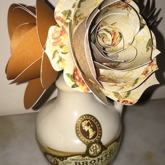 Small hand crafted paper flowers  in a repurposed  liquor flask