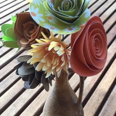 Small hand crafted paper flowers in a recycled vase