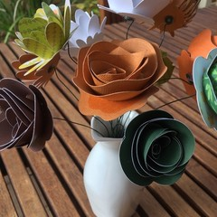 Small hand crafted paper flowers in a repurposed jug