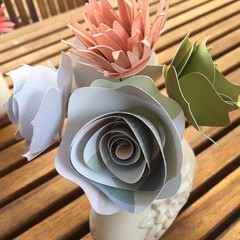 Small hand crafted paper flowers in a repurposed teapot