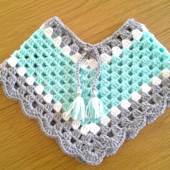 BABIES CROCHETED PONCHOS MADE TO FIT SIZE 0 TO 3 MONTHS.
