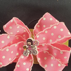 Pink spotted pinwheel bow with embellishment.