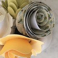 Small handcrafted paper flowers in a recycled vase