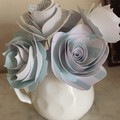 Small handcrafted paper flowers in a repurposed jug