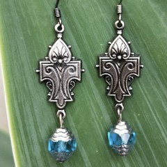 Fleur de lis metal earrings with blue Czech glass bead.