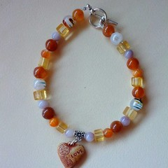 Brown / tan colored beaded bracelet with wooden heart charm