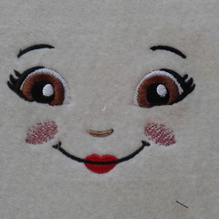 Embroidered doll face for DIY project.