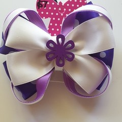 Purple triple layer fancy bow with embellishment.