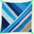 Baby blanket a patch of blue with bright green border and pompoms.