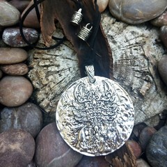 Pendant with large metal medallion with raised scorpion detail.