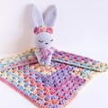 Bunny with rainbow lovey blanket.