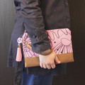 Pink floral clutch bag with wrist strap for women.