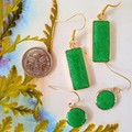 Emerald round and rectangular drop earrings set in gold.