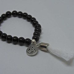 Glossy black beaded bracelet with white tassel and peace charm