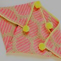 Baby neon pink dot blanket a patch trimmed in bright lemon with pompoms.