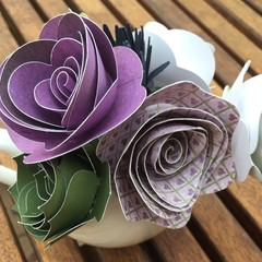 Small handcrafted paper flowers in a recycled jug