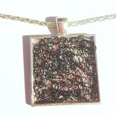 Unique black crochet wire in silver frame pendant necklace