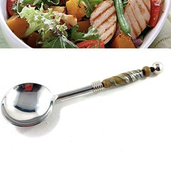 Stainless serving spoon with handmade glass embellishments.