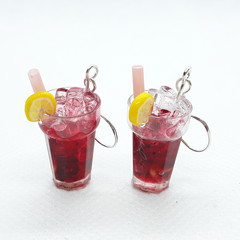 Strawberry juice earrings with sliced lemons and ice cube, miniature drink