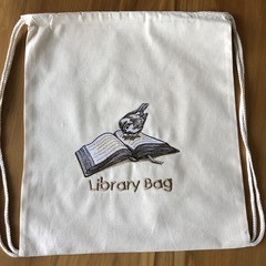 Calico library/toy bag with embroidered motif.