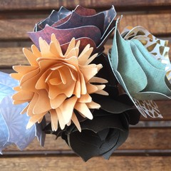 Small handcrafted paper flowers in a recycled salt shaker