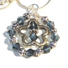 Silver and blue crystal with silver charm pendant and silver snake chain.