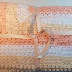 Crochet blanket in soft colours.