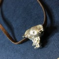 Dobby charm on a fitted brown choker