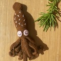 Tiny brown crochet squid with pink embroidery