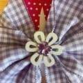 Purple checked pinwheel bow with embellishment.
